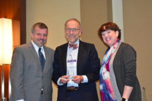 Dr. Irwin poses for a photo holding his MCHB Title V Lifetime Achievement Award